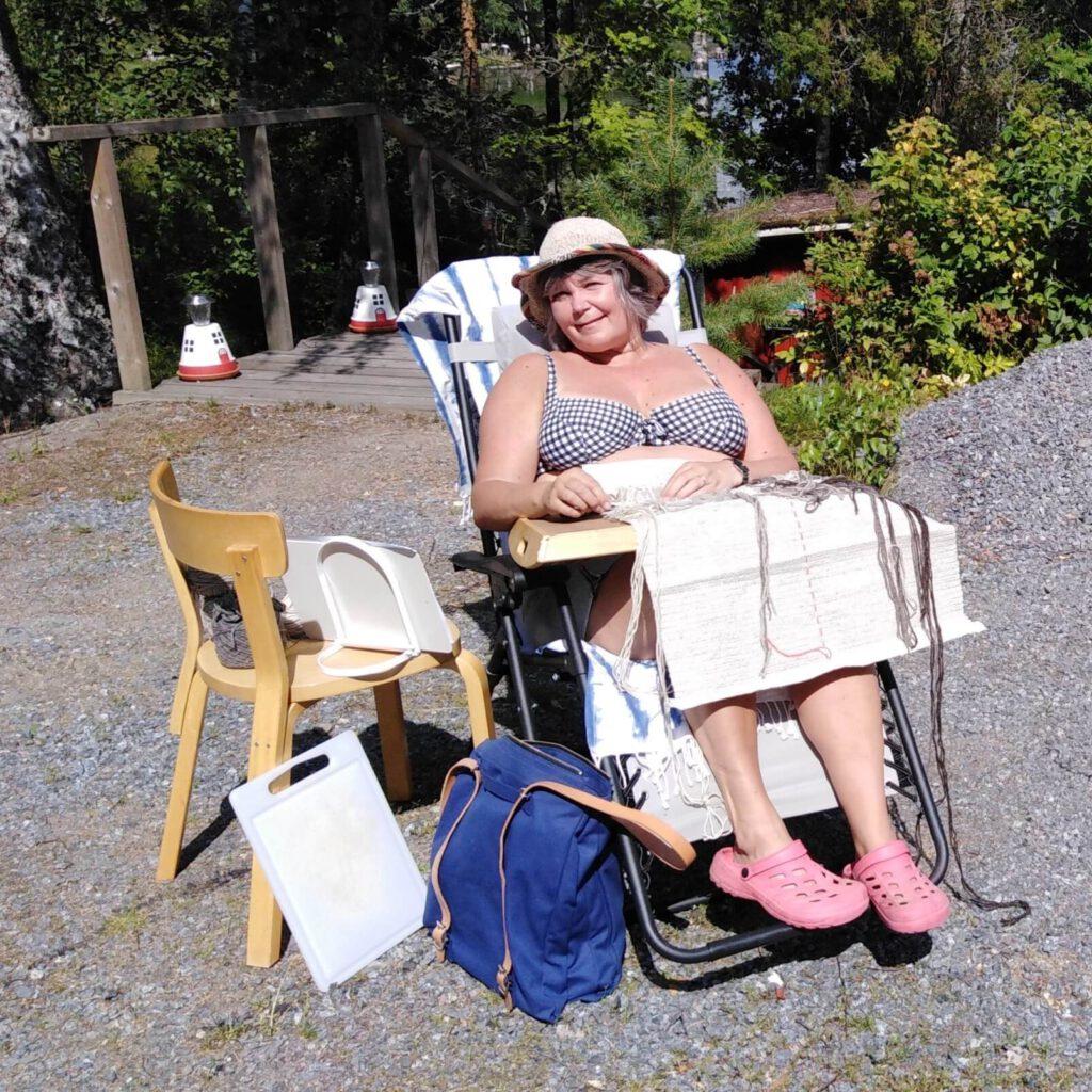 Paula ompelee ryijyä rannalla kesällä. Ryijyn tekeminen onnistuu missä vain.